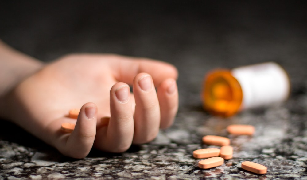 Hand with Bottle of Spilled Pills Due to Suicide